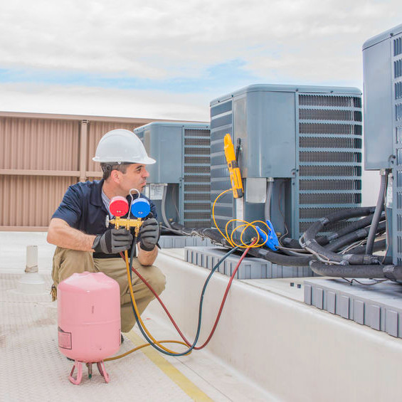 An HVAC tech charging rooftop units.