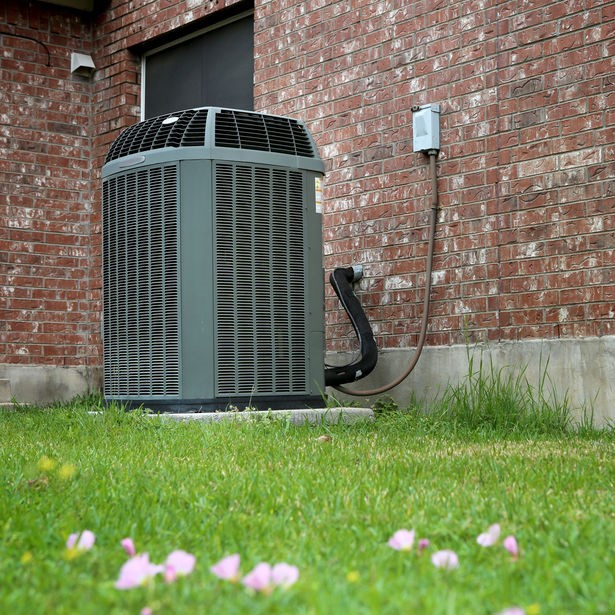 air conditioner system outside near wild flowers