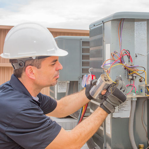 hvac technician checking capacitor on air conditioner