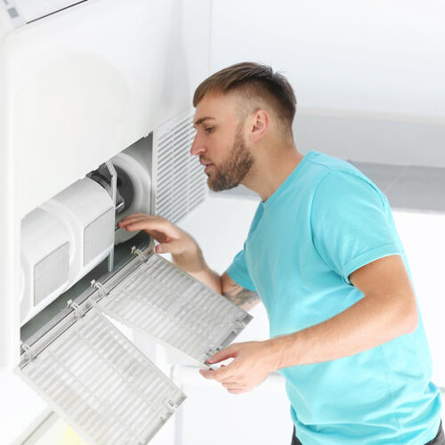 Young man investigating his air conditioning unit.